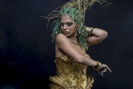 Sexy Latin woman with green hair and gold costume with handmade flourishes, fantasy image and tale
