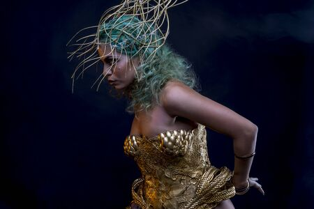 Mistic, Latin woman with green hair and gold tiara, wears a handmade warrior armor