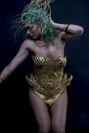 Goddess, Latin woman with green hair and gold costume with handmade flourishes, fantasy image and tale Stock Photo