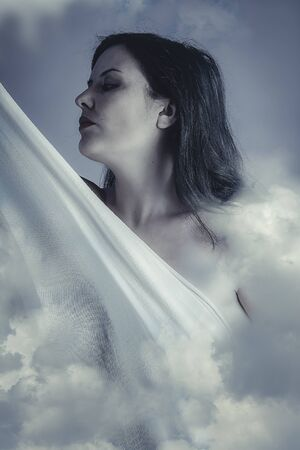 Beautiful woman in clouds, mithology concept. Brunette with long hair and white dress. photo