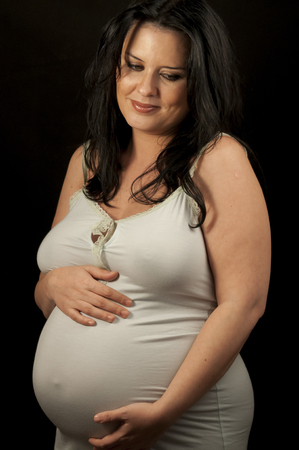 Happiness Beautiful pregnant brunette in light clothes showing signs of pregnancy photo