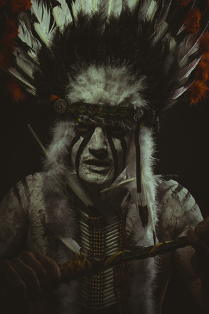 the americas: Aboriginal, American Indian with plume of feathers, ax and war paintings Stock Photo