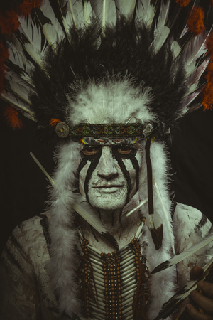 Costume Aboriginal, American Indian with plume of feathers, ax and war paintings Stock Photo