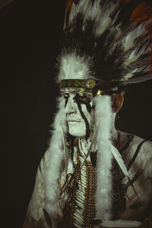 Aboriginal, American Indian with plume of feathers, ax and war paintings Stock Photo