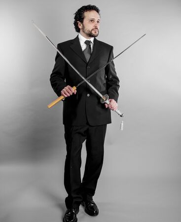 Corporate Businessman in black suit and armed japanese sword on gray background Stock Photo