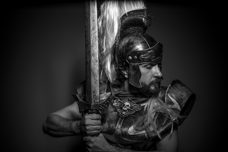 Roman centurion with armor and helmet with white chalk, steel sword and long red cape Stock Photo