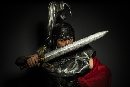 heritage protection: Glory, Roman centurion with armor and helmet with white chalk, steel sword and long red cape Stock Photo