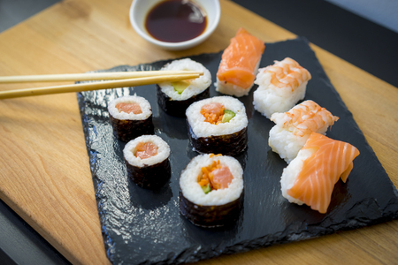 raw: Asian food, Sushi on a wooden table on black slate plate with soy sauce and chopsticks Stock Photo