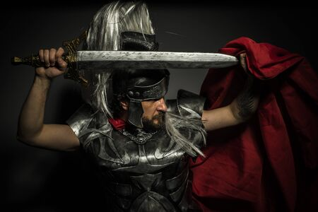 heritage protection: Gladiator, Roman centurion with armor and helmet with white chalk, steel sword and long red cape