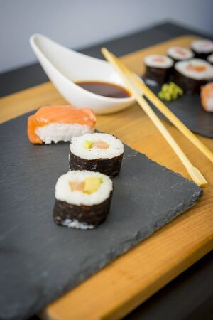 raw: Sushi on a wooden table on black slate plate with soy sauce and chopsticks
