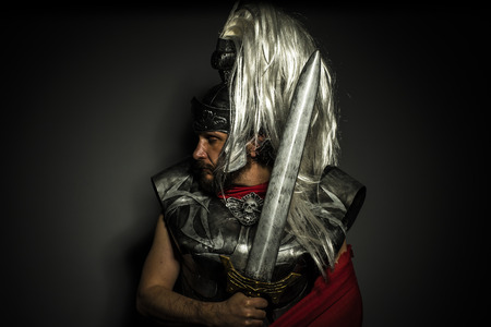 long: Roman centurion with armor and helmet with white chalk, steel sword and long red cape Stock Photo