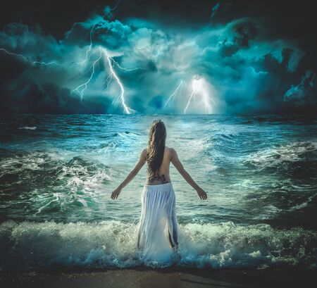 Elements, Brunette girl with bare chest looking back to the storm next to the mediterranean sea in Barcelona, Spain Stok Fotoğraf