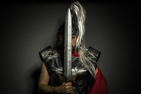 Empire, Roman centurion with armor and helmet with white chalk, steel sword and long red cape photo