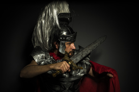 Roman centurion with armor and helmet with white chalk, steel sword and long red cape photo