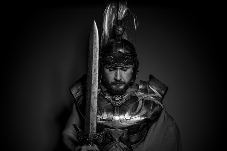 Army, Roman centurion with armor and helmet with white chalk, steel sword and long red cape photo