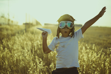 Young Boy playing to be airplane pilot, funny guy with aviator cap and glasses, carries in his hand a plane made of paper Stock Photo