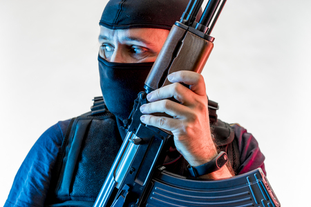 man armed with balaclava and bulletproof vest, gun and shotgun Stock Photo