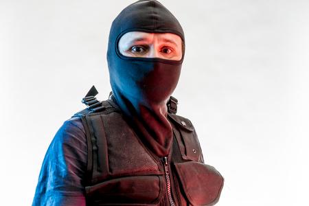 Thief, man armed with balaclava and bulletproof vest, gun and shotgun
