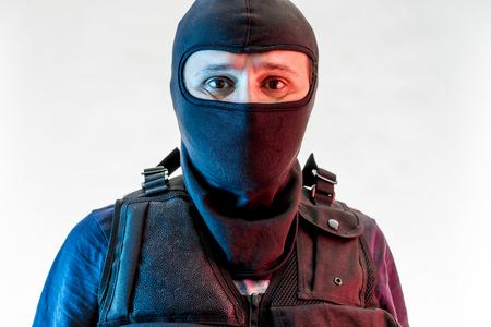 man armed with balaclava and bulletproof vest, gun and shotgun,