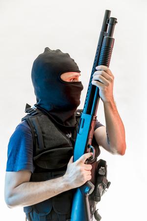 man armed with balaclava and bulletproof vest, gun and shotgun Stock Photo