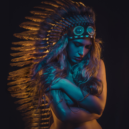 Shaman beautiful girl with plume of american indian feathers