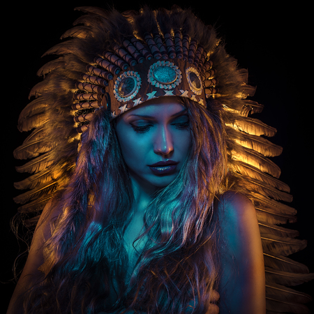 Colorful, beautiful girl with plume of american indian feathers