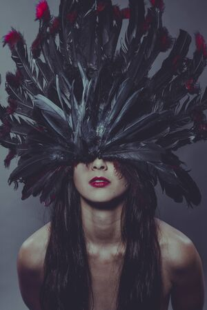 Masquerade, Nude brunette woman in a headdress made of big feathers in sensual and mysterious poses Stock Photo