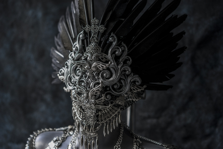 Steampunk, handmade piece, silver jewelry costume with chains and coins. wears a headdress made with feathers and gothic pieces Stock Photo