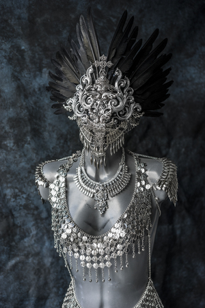 Fantasy, handmade piece, silver jewelry costume with chains and coins. wears a headdress made with feathers and gothic pieces Stock Photo