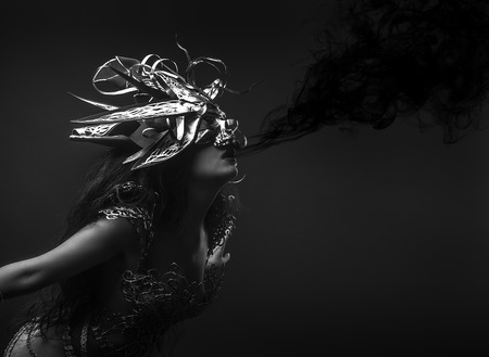 queen, black smoke, brunette woman dressed in goth style with a dress of golden threads and mask with skull Stock Photo