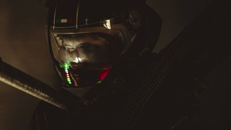 man of the future or space with futuristic helmet and fantasy lights, carries a laser weapon in his hands