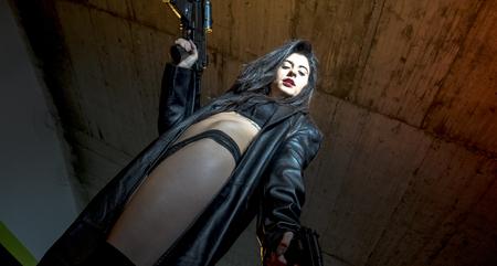 Espion, fille armée et dangereuse dans un parking, vêtue d'une veste en cuir noir et d'un gilet pare-balles