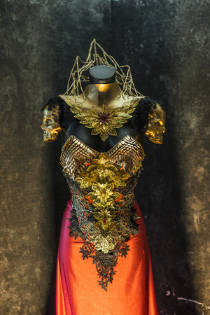 Medieval, fantastic gold armor and handmade metal pieces, it has a gold dragon scaled breastplate with a helmet of gothic pieces and red feathers, it has a red skirt and metal pieces of jewelery