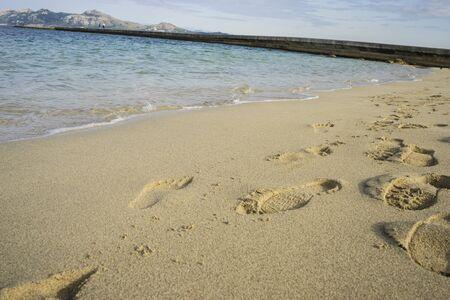Mediterranean scene, shore of the Mediterranean Sea with barefoot footprints of people in summer