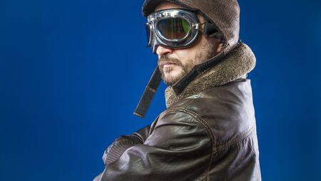 Proud, pilot of the 20s with sunglasses and vintage aviator helmet. Wears leather jacket, beard and expressive faces 스톡 콘텐츠