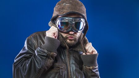 pilot of the 20s with sunglasses and vintage aviator helmet. Wears leather jacket, beard and expressive faces Stock Photo