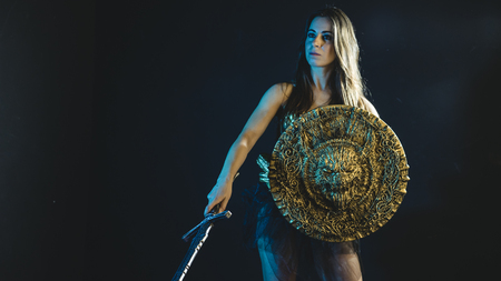 valkyrie warrior, woman with golden armor iron coat and big warrior sword Stock Photo