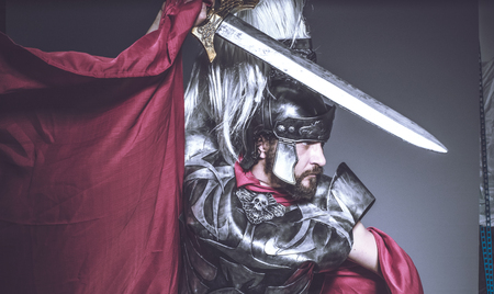 Roman gladiator, wrestler and warrior of Rome with helmet and red cloak, carries an iron sword, beard and long hair.