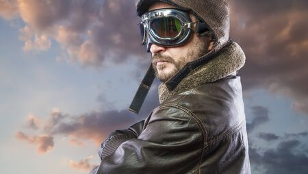 Proud, pilot of the 20s with sunglasses and vintage aviator helmet. Wears leather jacket, beard and expressive faces Stock Photo