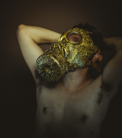 Man with gold gas mask and arabesques in poses of drowning and desperation, depression and psychiatry concept.