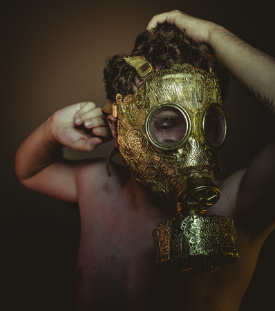 Atomic Man with gold gas mask and arabesques in poses of drowning and desperation, depression and psychiatry concept. Stock Photo