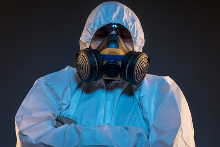 Quarantine, virus infection concept. Man in protective suit and antigas mask with glasses. Ebola, toxic gases, biological warfare, infections and diseases Foto de archivo