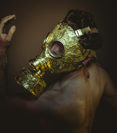 Protective, Man with gold gas mask and arabesques in poses of drowning and desperation, depression and psychiatry concept. Stock Photo
