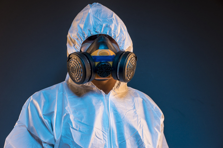 Virus infection concept. Man in protective suit and antigas mask with glasses. Ebola, toxic gases, biological warfare, infections and diseases Stock Photo