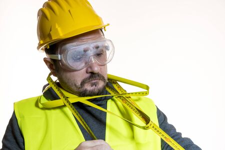 juggling a man who wants to do a work without knowledge, work without experience.Man dressed in yellow builder helmet with protective glasses ready to start the construction work