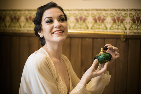 smell perfume bottle, old bath room, brunette woman in antique silk nightdress and hairstyle in the style of the 20s Stockfoto