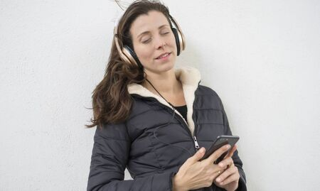Lifestyle, Brown-haired woman listening to music with the mobile. enjoying music with golden and white helmets on the street in winter Imagens