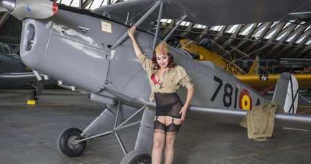 redhead woman dressed as a soldier next to a plane of the second world war, American pinup in the style of the 40s. sensual and sexy woman Editorial