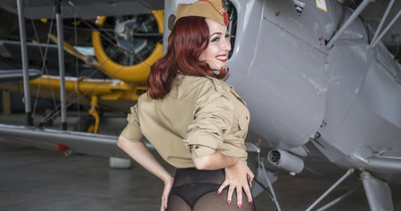 Airplane, redhead woman dressed as a soldier next to a plane of the second world war, American pinup in the style of the 40s. sensual and sexy woman