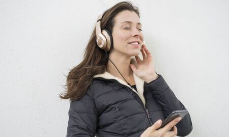 Lifestyle, Brown-haired woman listening to music with the mobile. enjoying music with golden and white helmets on the street in winter Banco de Imagens